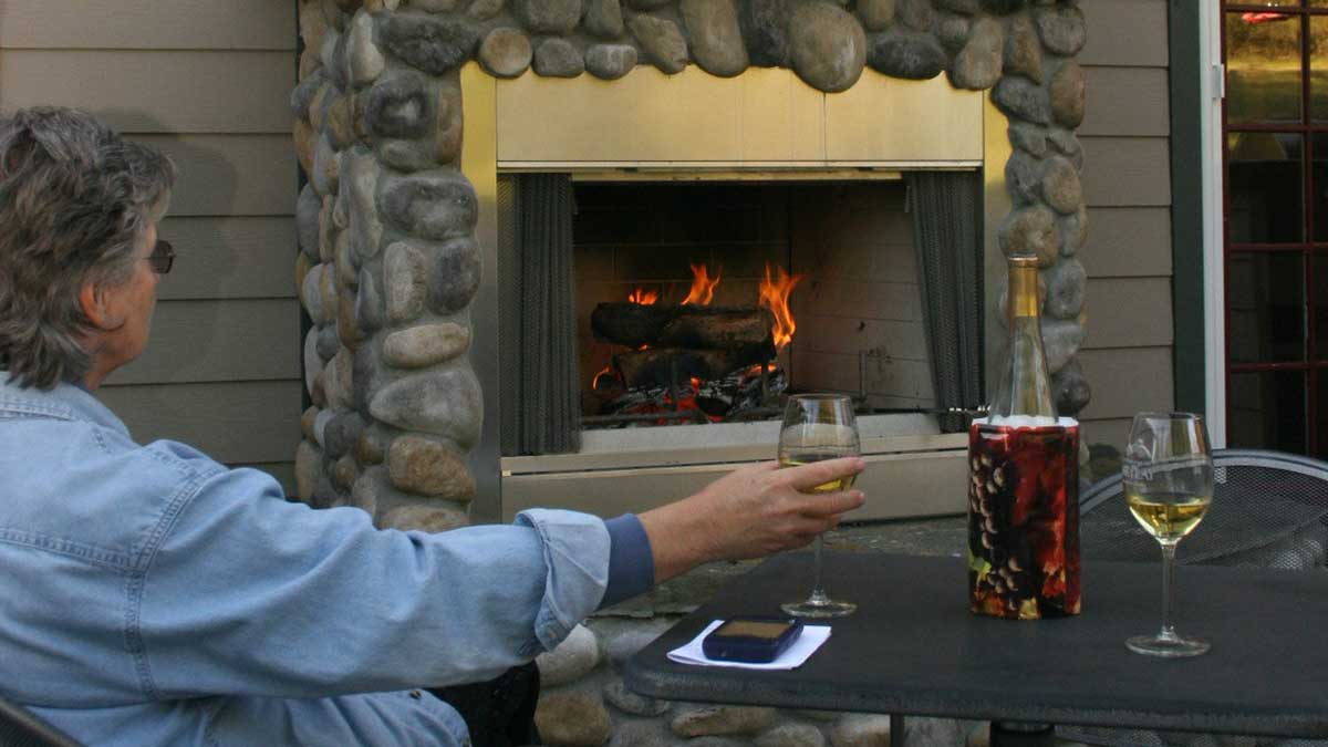 A woman in a blue shirt holding a glass of white wine enjoying the outdoor fireplace.