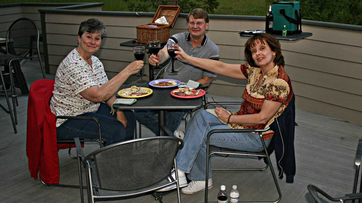 Two women and one woman sitting at a patio table toasting with glasses of red wine.