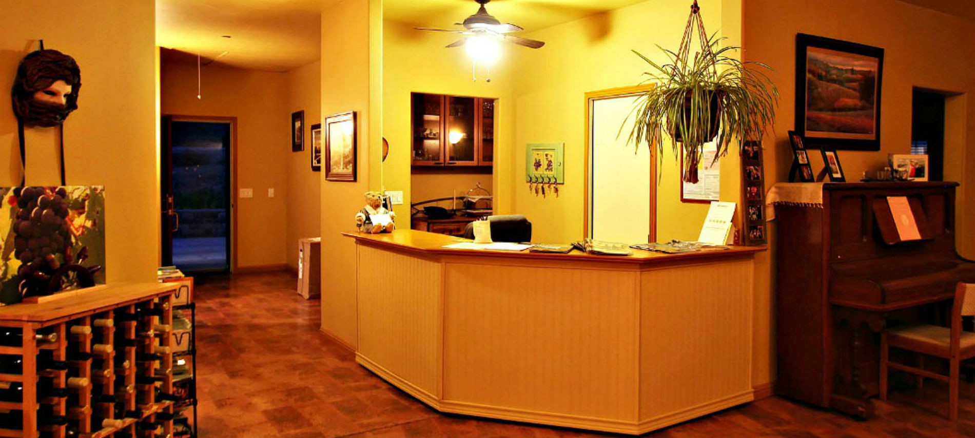 Lucinda's Reception desk next to the Great Room with the yellow wall and brown floor