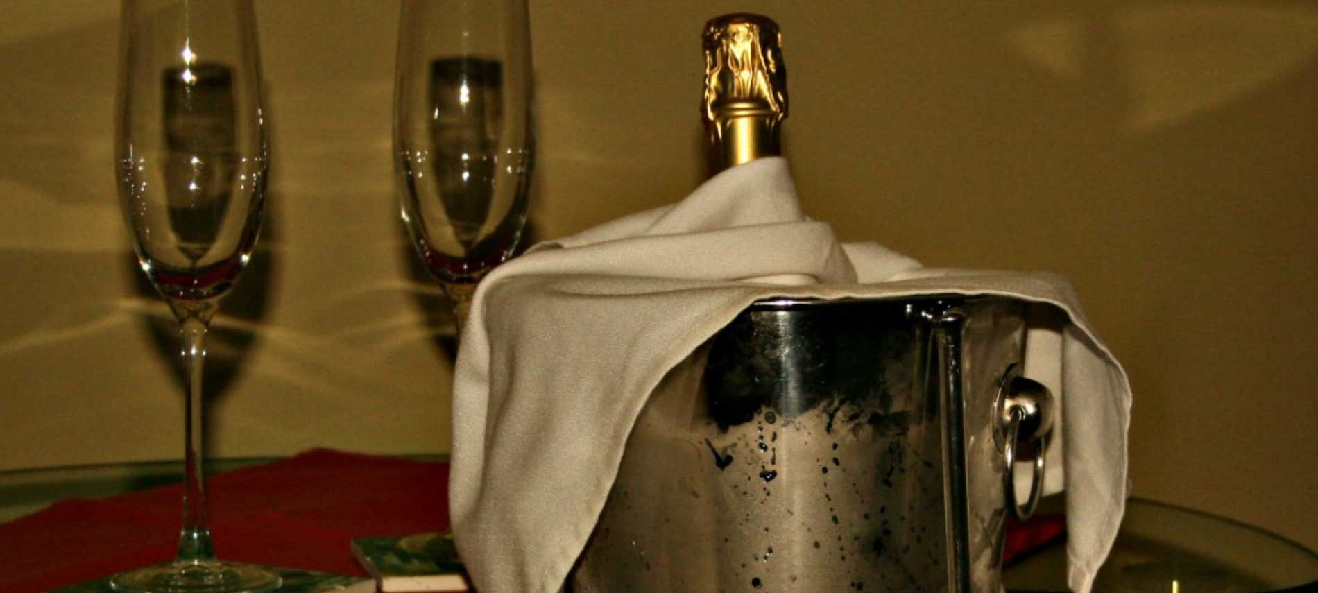A Chiller Bucket filled with a Champagne bottle and two glasses setting on a table