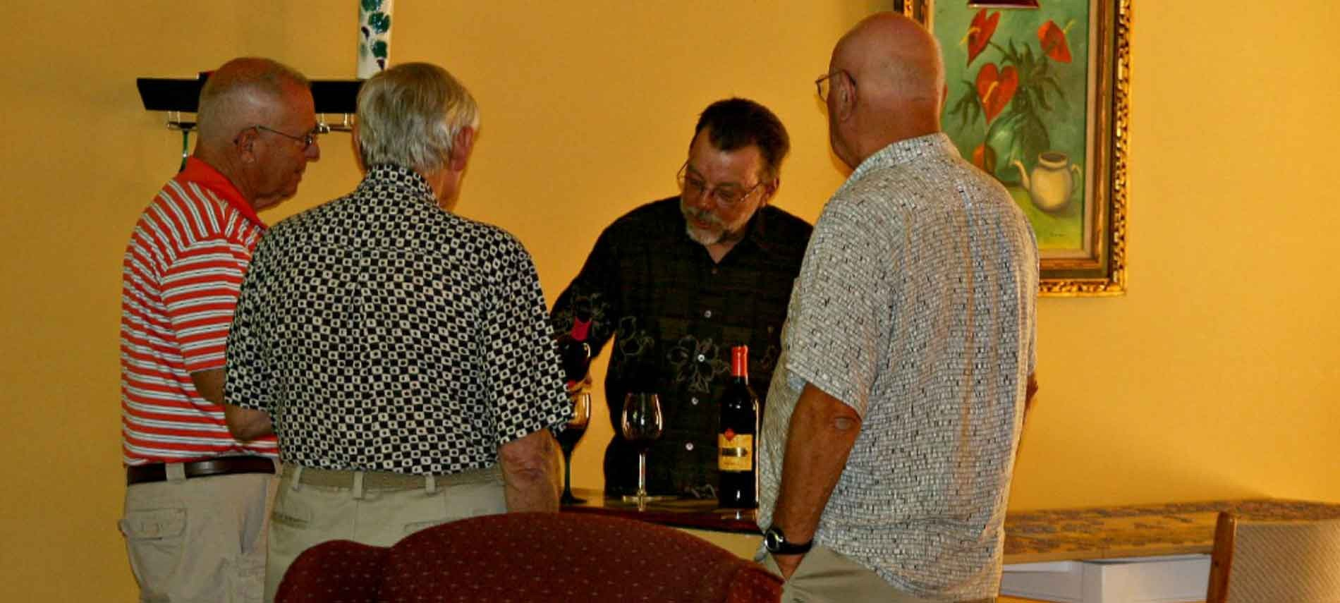 Three men standing with back to camera with a man pouring wine in a yellow colored room