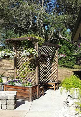 The Redwood Trellis & Benches on a Patio with a Planter box & Flowers and Hanging Flower Pots with lots of blooms