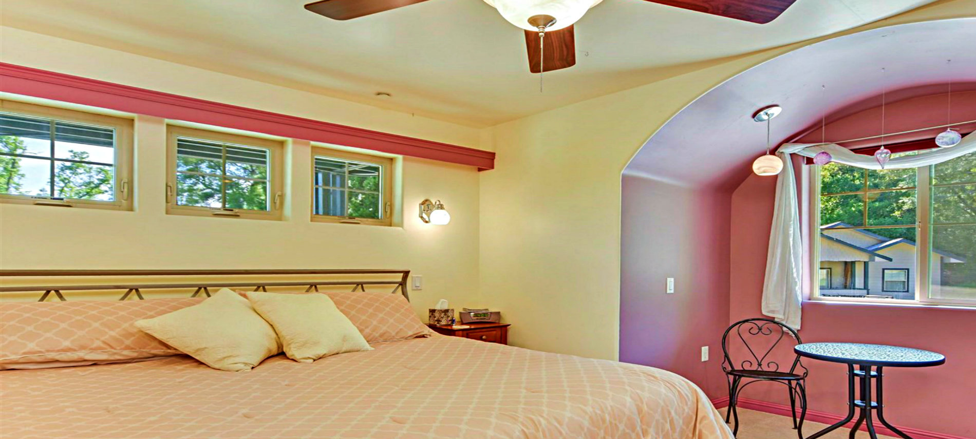 Bed with Tan Spread and Pillows at Head of Bed and a Lace Draping from Ceiling to Corners of Bed