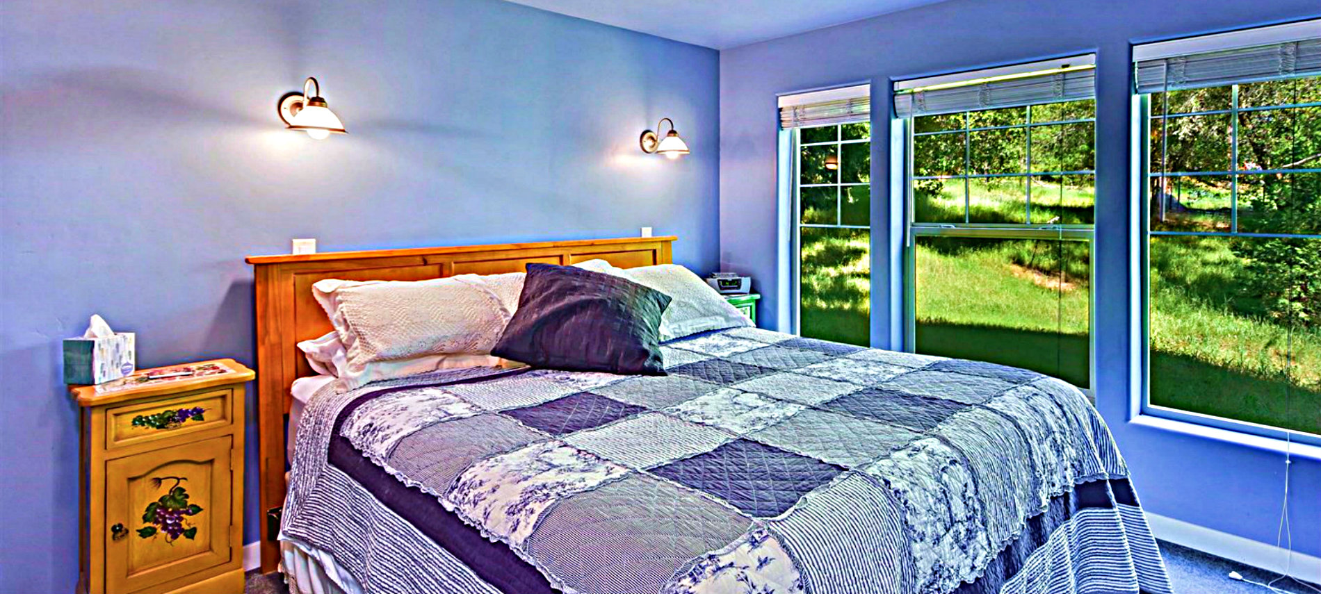 Bed with white & pink spread with several shaped pillows and tables on each side and a blue wall