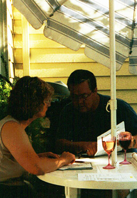 A man and woman at a patio table with umbrella and working material on the table with wine glasses.