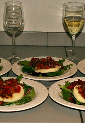 Plates of Salad Greens with Eggplant w-Tomato Relish on a counter